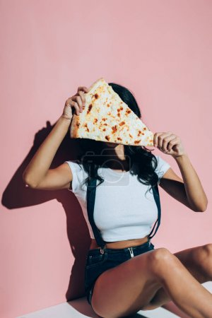 obscured view of woman covering face with piece of pizza on pink background