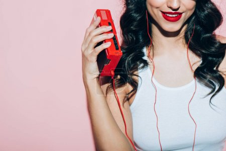 partial view of smiling woman with retro music player on pink backdrop