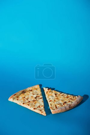 close up view of pieces of cooked pizza isolated on blue