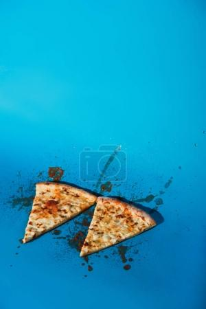 close up view of pieces of cooked pizza on blue backdrop