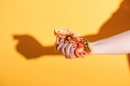 Photo for Partial view of woman squeezing piece of pizza in hand on yellow background - Royalty Free Image
