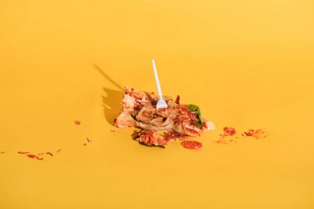 close up view of disposable fork in smashed piece of pizza on orange backdrop