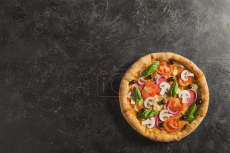 Photo for Top view of cooked italian pizza on dark tabletop - Royalty Free Image
