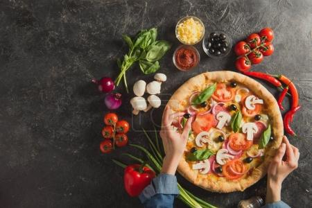 Photo for Cropped shot of woman putting black olives on italian pizza on dark tabletop - Royalty Free Image
