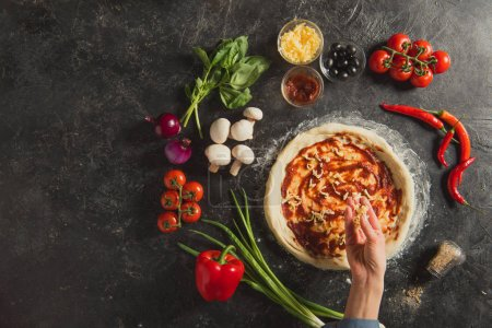 Photo for Cropped shot of woman putting grated cheese on dough while cooking italian pizza on dark tabletop - Royalty Free Image