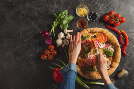 Photo for Cropped shot of woman cutting cooked italian pizza with fresh ingredients on dark tabletop - Royalty Free Image