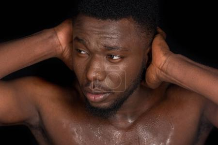 young bare chested sweaty african american man closing ears with hands and looking away isolated on black