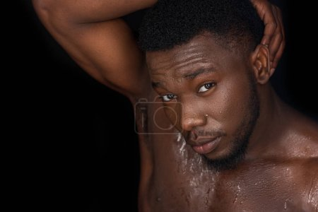 sweaty bare chested young african american man posing and looking at camera isolated on black