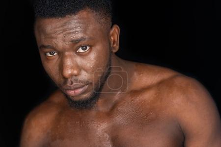 sweaty shirtless young african american man looking at camera isolated on black