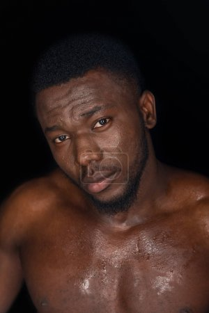 handsome sweaty young african american man looking at camera isolated on black