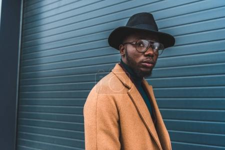 Photo for Stylish young african american man in hat and overcoat looking at camera - Royalty Free Image