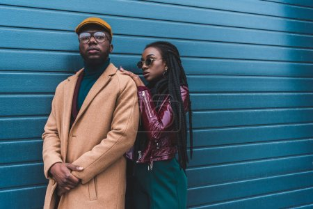 beautiful african american couple in fashionable outfit posing together outside