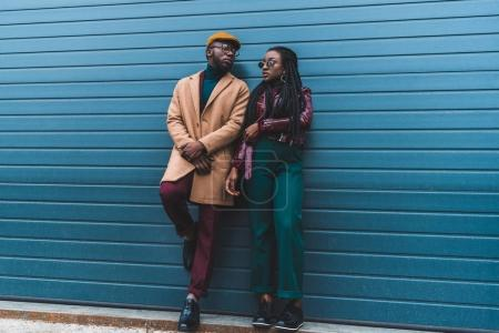 full length view of stylish african american couple in jacket and overcoat posing together on street