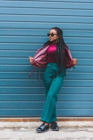 Photo pour Belle jeune femme afro-américaine en lunettes de soleil posant dans la rue - image libre de droit