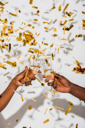 cropped shot of african american couple clinking glasses of champagne on white with golden confetti