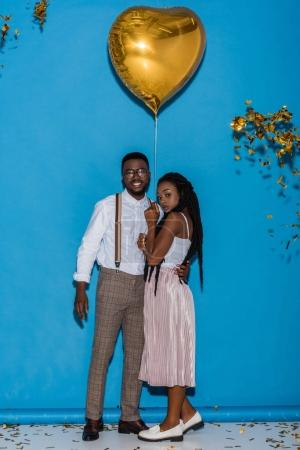 stylish young african american couple posing with golden heart shaped balloon on blue