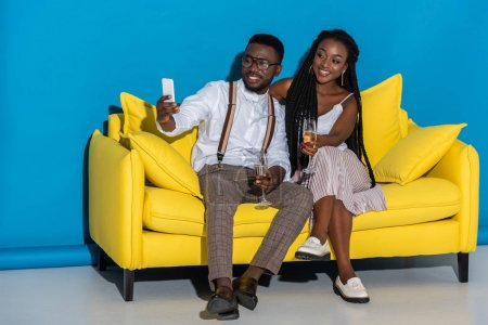 smiling young african american couple holding glasses of wine and taking selfie with smartphone on couch