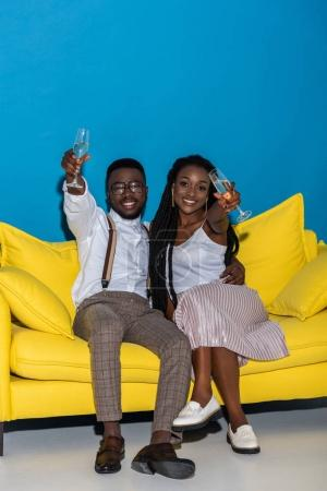 happy stylish african american couple drinking champagne and smiling at camera while sitting on sofa