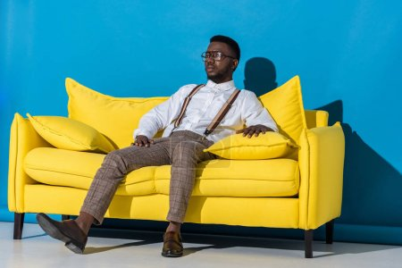 handsome stylish young african american man sitting on yellow couch and looking away on blue