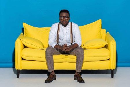 Photo pour Jeune homme afro-américain à lunettes assise sur le canapé et regarder la caméra - image libre de droit