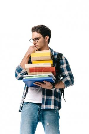 pensive handsome student holding stack of books isolated on white