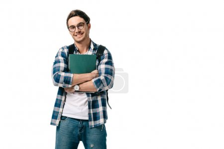 smiling handsome student holding copybook and looking at camera isolated on white