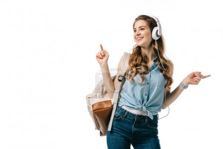 beautiful student listening to music with headphones and dancing isolated on white