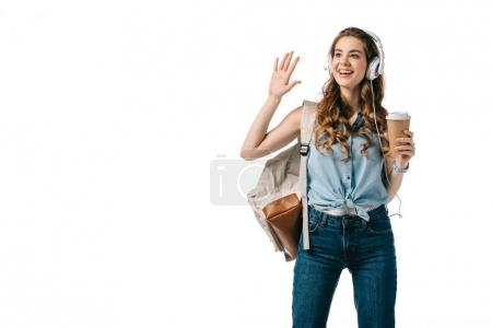 smiling beautiful student waving hand and listening to music isolated on white