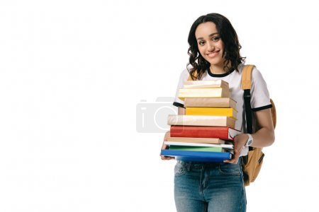 smiling african american teen student holding stack of books isolated on white