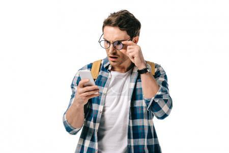 Photo for Shocked handsome student looking at smartphone isolated on white - Royalty Free Image