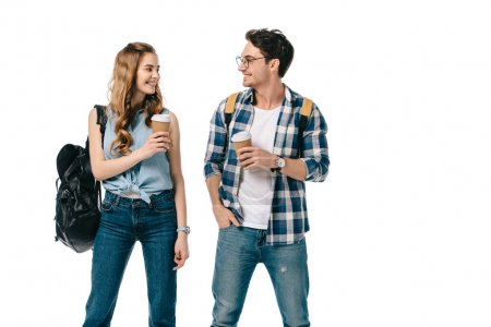 smiling young students holding coffee to go and looking at each other isolated on white