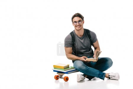 smiling handsome student sitting on skate and holding book on white