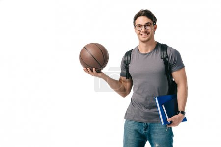 smiling handsome student holding basketball ball isolated on white