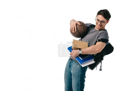 confused handsome student holding books and basketball ball isolated on white