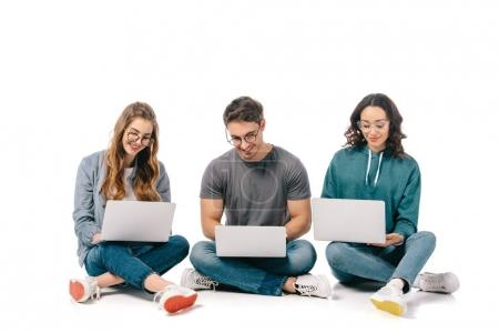 Photo pour Heureux étudiants multiculturels en utilisant des ordinateurs portables sur blanc - image libre de droit