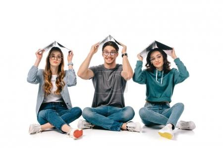 smiling multicultural students sitting with books above heads on white