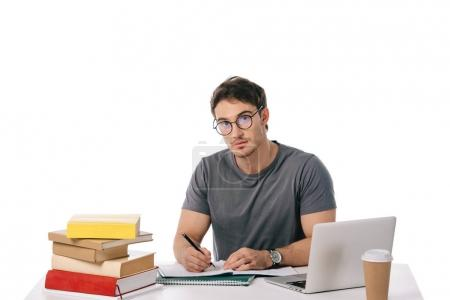Foto de Estudiante guapo escribiendo en mesa aislado en blanco - Imagen libre de derechos