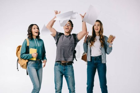 smiling multicultural students looking at falling paper on white