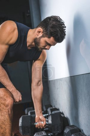 Side view of young sportsman raising dumbbell in sports hall