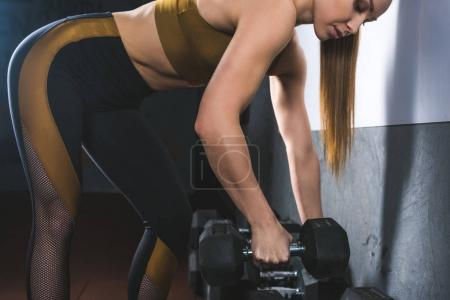 Cropped image of young sportswoman raising dumbbell in sports hall