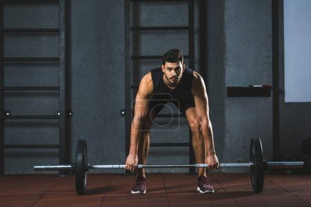 Front view of young sportsman preparing to raise barbell in sports hall