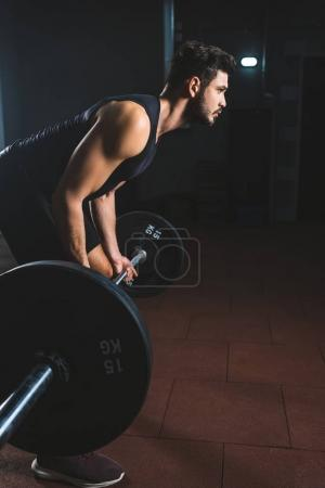 Photo for Side view of young bodybuilder holding barbell in sports hall - Royalty Free Image