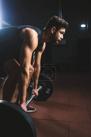Photo for Side view of young athlete preparing to raise barbell in sports hall - Royalty Free Image