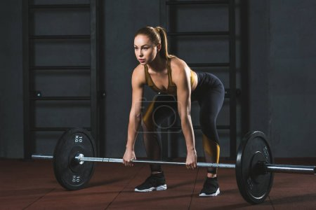Front view of young sportswoman preparing to raise barbell in sports hall