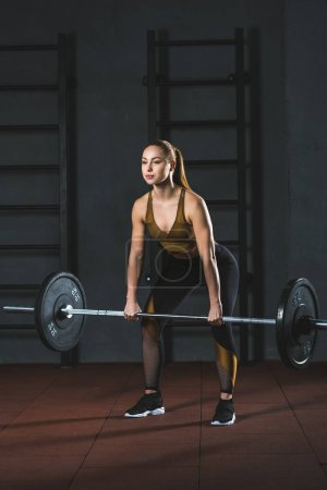 Front view of young sportswoman exercising with barbell in sports hall