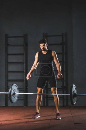 Young caucasian sportsman letting go barbell in sports hall