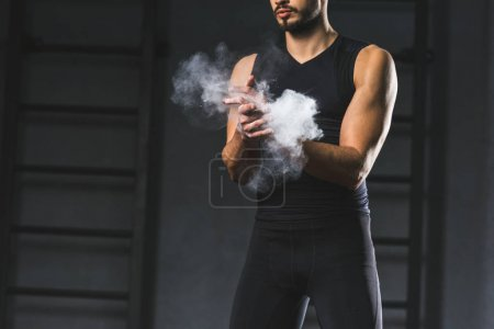 Cropped image of young sportsman spreading chalk powder in hands  in sports hall