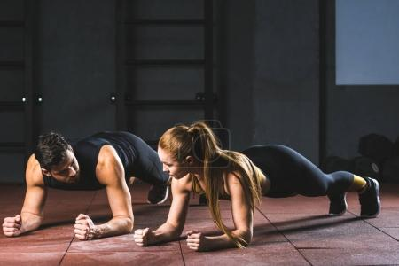 Photo for Front view of young sportswoman and sportsman doing push ups in sports hall - Royalty Free Image