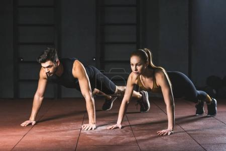 Photo for Sportswoman and sportsman doing push ups in gym in sports hall - Royalty Free Image