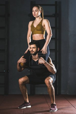 Young sportsman doing squats with woman on shoulder in sports hall